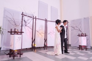 the newly weds standing against the fine japanese screens dad made for the wedding