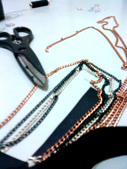 some bronze, silver and black chains with black ribbon and a pair of scissor